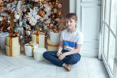 Young boy opens a gift under a Christmas tree Stock Images