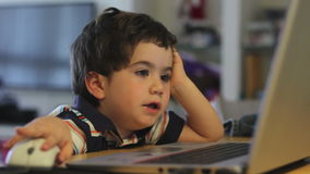 Young boy operating educational game on a laptop stock video footage
