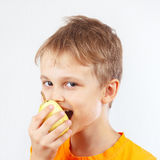 Young boy in orange shirt eating a juicy yellow pear Royalty Free Stock Photography
