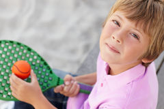 Young boy outdoors with bat and ball. Looking at camera Stock Photos