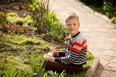 Young boy outdoors on the grass at backyard using his tablet com Stock Photography