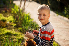 Young boy outdoors on the grass at backyard using his tablet com Royalty Free Stock Images