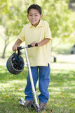 Young boy outdoors on scooter smiling Stock Photos