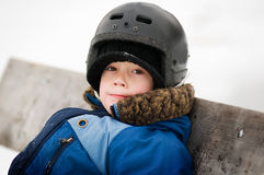 Young boy outdoors wearing a hockey helmet. Five year old boy sitting on a bench at an outdoor skating rink wearing a hockey helmet Royalty Free Stock Photography