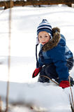 Young boy outdoors in the winter. Little boy playing outdoors in the snow wearing warm winter clothing Royalty Free Stock Photos