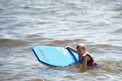 A young boy paddles along in the water on a paddleboard royalty free stock image