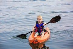 Young Boy paddling a kayak on a beautiful lake Royalty Free Stock Image
