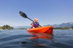 Young Boy paddling a kayak on a beautiful mountain lake Royalty Free Stock Photos