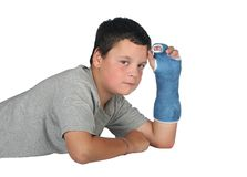 Young boy in pain in cast. Young boy wearing a cast with a tear coming from his eye due to the pain Royalty Free Stock Image