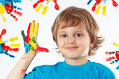 Young boy with painted hands on background of hand prints Royalty Free Stock Image