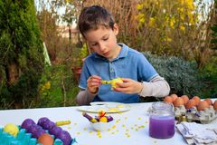 A young boy painting Easter eggs outdoor in France. Easter children creative activity. A young boy painting Easter eggs outdoor in France. Easter children royalty free stock image