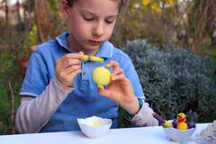 A young boy painting Easter eggs outdoor in France. Easter children creative activity. A young boy painting Easter eggs outdoor in France. Easter children stock photography