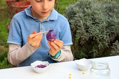 A young boy painting Easter eggs outdoor in France. Easter children creative activity.  royalty free stock image