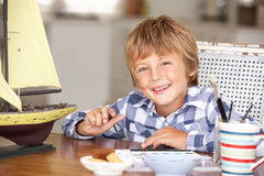 Young boy painting model ship Royalty Free Stock Photos