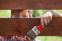 Young boy painting the wooden fence Royalty Free Stock Photography