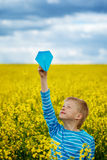 Young boy with paper airplane against blue sky Royalty Free Stock Photo