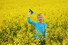 Young boy with paper airplane against blue sky Stock Photography
