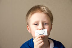 Young boy with paper smile Royalty Free Stock Photos