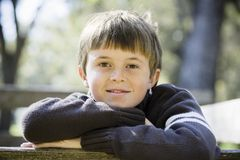 Young Boy in Park. Portrait of a Cute Young Boy Leaning on a Wooden Railing Smiling Directly To Camera Royalty Free Stock Photo