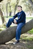 Young Boy in Park. Young Boy Sitting on Tree Trunk in Park Stock Images