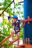 Young boy passing the cable route high among trees, extreme sport in adventure park Stock Photography