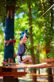 Young boy passing the cable route high among trees, extreme sport in adventure park Royalty Free Stock Image