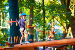 Young boy passing the cable route high among trees, extreme sport in adventure park Stock Image