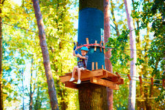 Young boy passing the cable route high among trees, extreme sport in adventure park. Young boy, kid passing the cable route high among trees, extreme sport in Stock Photo