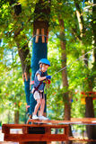Young boy passing the cable route high among trees, extreme sport in adventure park Stock Photos