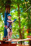 Young boy passing the cable route high among trees, extreme sport in adventure park Royalty Free Stock Photography
