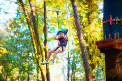 Young boy passing the cable route high among trees, extreme sport in adventure park. Young boy, kid passing the cable route high among trees, extreme sport in Royalty Free Stock Photo