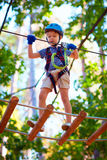 Young boy passing the cable route high among trees, extreme sport in adventure park Royalty Free Stock Photos