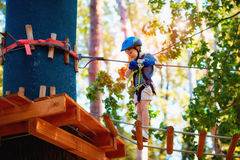 Young boy passing the cable route high among the trees, extreme sport in adventure park. Young kid boy passing the cable route high among the trees, extreme Stock Photography