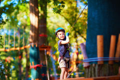 Young boy passing the cable route high among the trees, extreme sport in adventure park. Young kid boy passing the cable route high among the trees, extreme Royalty Free Stock Image