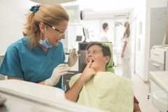 Young boy Patient at the dentist. Young boy Patient is smiling while Senior male dentist getting ready to check his teeth at the dentistry. Healthcare concept Stock Image