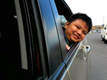 Young boy peeking or looking out a car window. Photo of a young boy peeking or looking out a car window royalty free stock photos