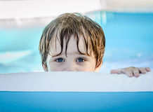 A young boy peeking out. A young boy with blue eyes peeking out over the side of a pool Stock Photos