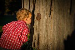 Young Boy Peeks Inside Barn Royalty Free Stock Photos
