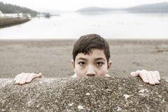 Young boy peeks over a wall. Stock Photos