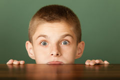 Young boy peeping out the table Stock Images