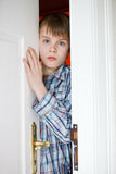 Young boy peering through a partially opened door Royalty Free Stock Photo