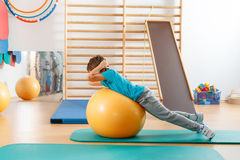 Young boy performs exercises Royalty Free Stock Image