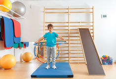 Young boy performs exercises with hula hoop Stock Image