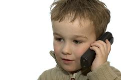 Young boy on phone 1. A 5-year old calling his grandma. He is listening very careful. On white background stock photos