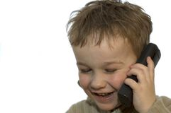 Young boy on phone 2. A 5-year old calling his grandma. He is listening and laughing. On white background stock photography