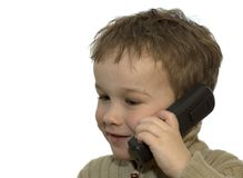 Young boy on phone 3. A 5-year old calling his grandma. He is listening very careful. On white background stock image