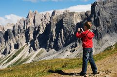 Young boy photographing mountains. Passo Giau,  Italy Royalty Free Stock Photos