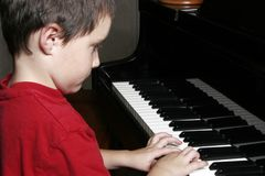 A Young Boy at the piano royalty free stock image