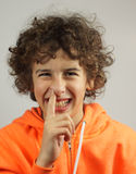 A young boy picks his nose. A young boy is picking his nose with a cheeky smile Stock Photos