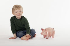 Young Boy and a Piggy Bank on the Floor Royalty Free Stock Image